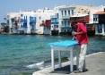 Man Painting Blue Door Mykonos Greece